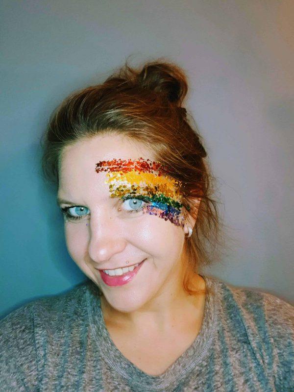 vrouw met pride glitter op gezicht