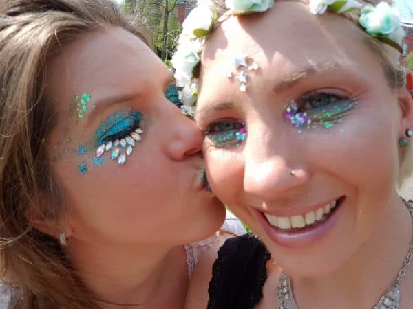 meisje geeft ander meisje kusje op de wang, beide met heel veel glitter op het gezicht